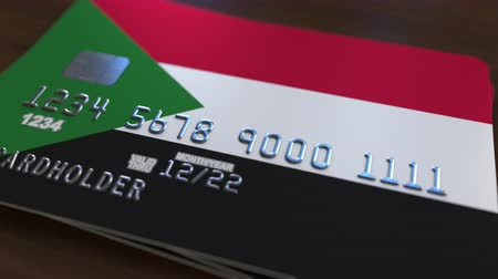 sudanian : Plastic bank card featuring flag of Sudan. Sudanian national banking system related animation Stock Footage