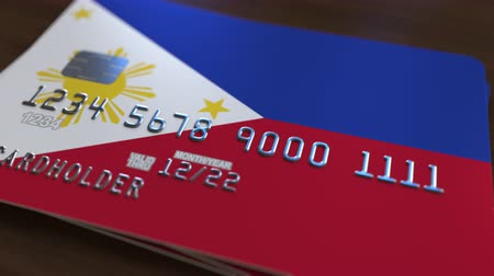 defocus : Plastic bank card featuring flag of Philippines. National banking system related animation
