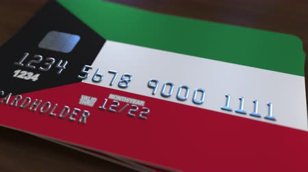 debit : Plastic bank card featuring flag of Kuwait. Kuwaiti national banking system related animation