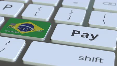 дебет : Bank card featuring flag of Brazil as a key on a computer keyboard. Brazilian online payment conceptual animation