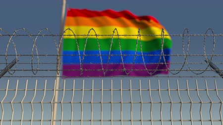 oppression : Barbed wire against blurred waving gay pride flag. LGBT oppression conceptual loopable 3D animation Stock Footage
