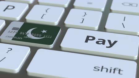 Пакистан : Bank card featuring flag of Pakistan as a key on a computer keyboard. Pakistani online payment conceptual animation