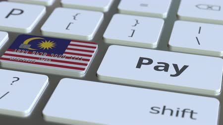 электронная коммерция : Bank card featuring flag of Malaysia as a key on a computer keyboard. Malaysian online payment conceptual animation