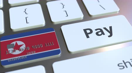 dprk : Bank card featuring flag of North Korea as a key on a computer keyboard. Online payment conceptual animation Stock Footage