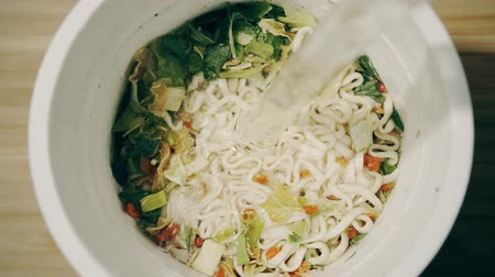 ramen : Pouring hot water into cup with instant noodles, top down view Stock Footage