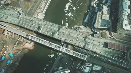 multiple lane : Aerial down view of cars moving along the bridge across icy river