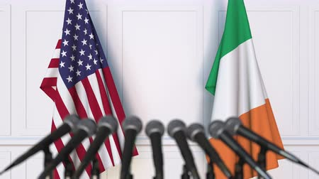 press conference : Flags of the United States and Ireland at international meeting or negotiations press conference. 3D animation Stock Footage