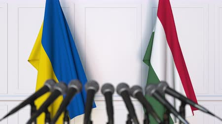 венгерский : Flags of Ukraine and Hungary at international meeting or negotiations press conference. 3D animation