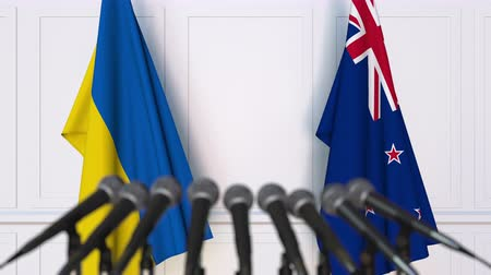 nowa zelandia : Flags of Ukraine and New Zealand at international meeting or negotiations press conference. 3D animation