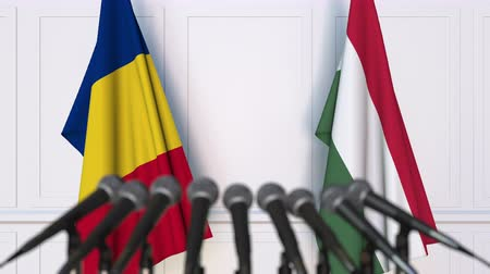 romeno : Flags of Romania and Hungary at international meeting or negotiations press conference. 3D animation