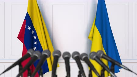 konferans : Flags of Venezuela and Ukraine at international meeting or negotiations press conference. 3D animation