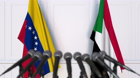 mededeling : Flags of Venezuela and Sudan at international meeting or negotiations press conference. 3D animation Stockvideo