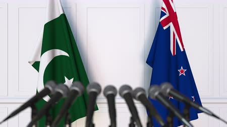 nowa zelandia : Flags of Pakistan and New Zealand at international meeting or negotiations press conference. 3D animation
