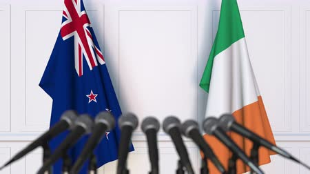 nowa zelandia : Flags of New Zealand and Ireland at international meeting or negotiations press conference. 3D animation Wideo