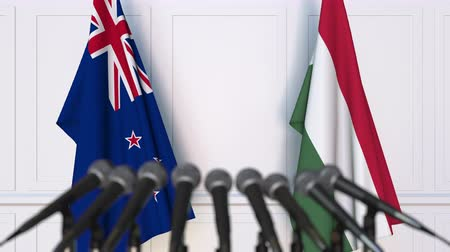 press conference : Flags of New Zealand and Hungary at international meeting or negotiations press conference. 3D animation Stock Footage