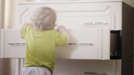 pokus : Funny baby girl takes her clothes from the dressers drawer