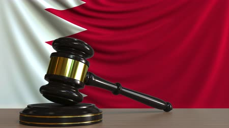 adli : Judges gavel and block against the flag of Bahrain. Bahraini court conceptual animation