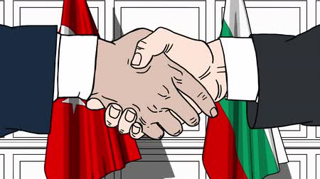 búlgaro : Businessmen or politicians shake hands against flags of Turkey and Bulgaria. Official meeting or cooperation related cartoon animation