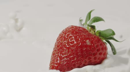 lezzet : Straberry falls into milk, slow motion close-up. Shot on Red Stok Video
