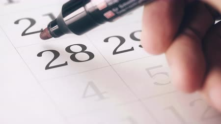 escrever : Drawing red circled mark on the twenty-eighth 28 day of a month in the calendar