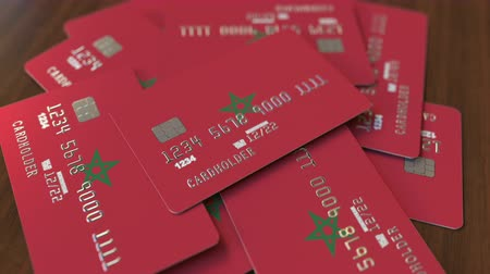 дебет : Pile of credit cards with flag of Morocco. Moroccan banking system conceptual 3D animation