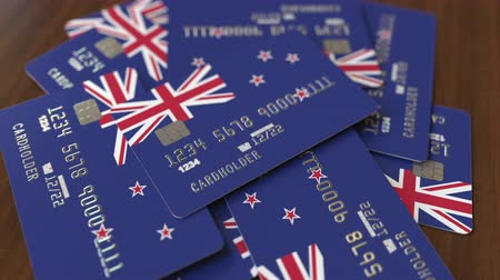 pile of money : Pile of credit cards with flag of New Zealand. National banking system conceptual 3D animation Stock Footage