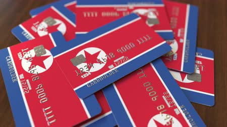 corée du nord : Pile of credit cards with flag of North Korea. National banking system conceptual 3D animation Vidéos Libres De Droits