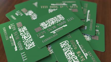 заем : Pile of credit cards with flag of Saudi Arabia. National banking system conceptual 3D animation Стоковые видеозаписи