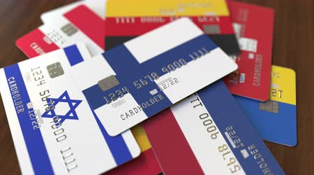 перевод : Many credit cards with different flags, emphasized bank card with flag of Finland