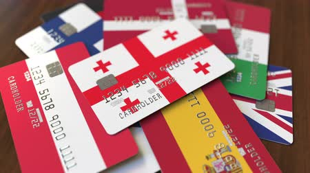 дебет : Many credit cards with different flags, emphasized bank card with flag of Georgia