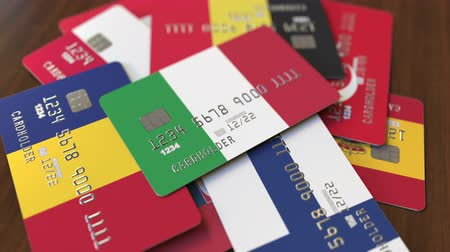 pile of money : Many credit cards with different flags, emphasized bank card with flag of Italy