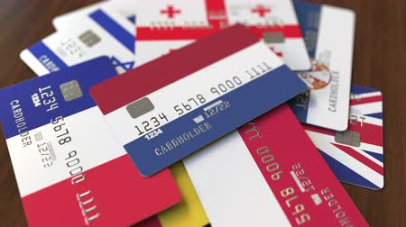 pile of money : Many credit cards with different flags, emphasized bank card with flag of the Netherlands