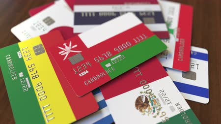 перевод : Many credit cards with different flags, emphasized bank card with flag of Oman