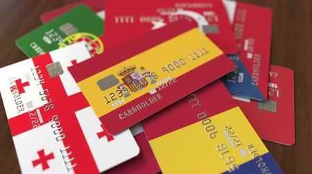 перевод : Many credit cards with different flags, emphasized bank card with flag of Spain