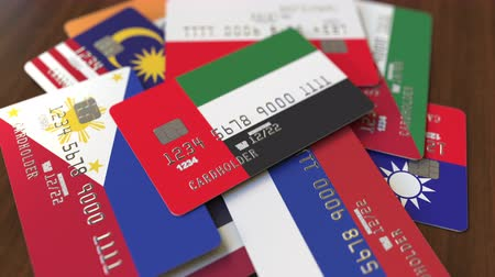 pile of money : Many credit cards with different flags, emphasized bank card with flag of the United Arab Emirates UAE