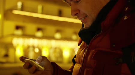 lélegzet : Handsome young man in red jacket watches photos on his smartphone in the evening