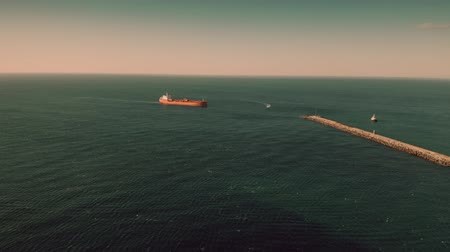 marine technology : Aerial view of unknown red oil tanker moving at sea near seaport