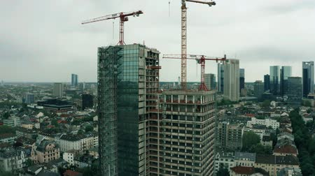 crane fly : FRANKFURT AM MAIN, GERMANY - APRIL 29, 2019. Aerial view of a modern building construction site Stock Footage