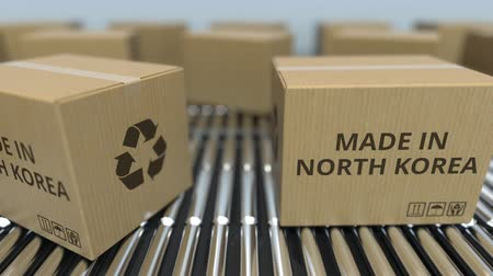dprk : Cartons with MADE IN NORTH KOREA text on roller conveyor. Korean goods related loopable 3D animation
