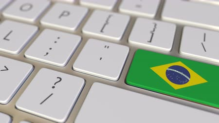 kapcsoló : Key with flag of Brazil on the computer keyboard switches to key with flag of the USA, translation or relocation related animation Stock mozgókép