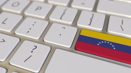 relocate : Key with flag of Venezuela on the computer keyboard switches to key with flag of the USA, translation or relocation related animation Stock Footage