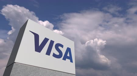 visa : Logo of VISA on a stand against cloudy sky, editorial animation