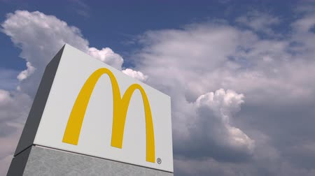 mcdonalds : Logo of MCDONALDS on a stand against cloudy sky, editorial animation