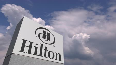 hilton : Logo of HILTON on a stand against cloudy sky, editorial animation Stock Footage