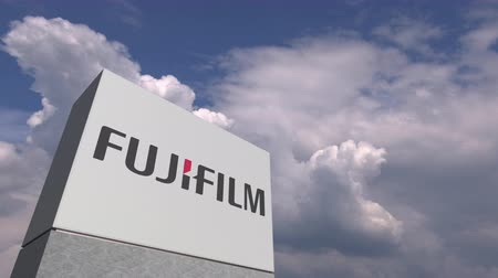 oficial : Logo of FUJIFILM on a stand against cloudy sky, editorial animation
