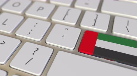 иммиграция : Key with flag of the United Arab Emirates UAE on the computer keyboard switches to key with flag of Great Britain, translation or relocation related animation