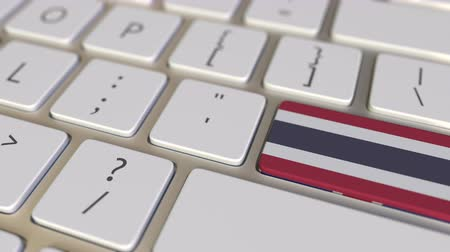 deslocalização : Key with flag of Thailand on the computer keyboard switches to key with flag of Great Britain, translation or relocation related animation Stock Footage