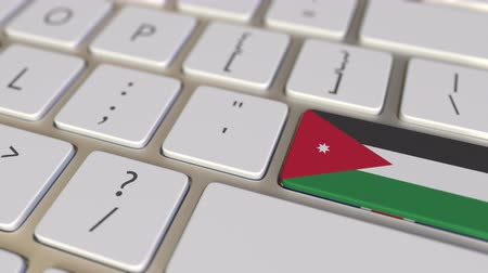 relocate : Key with flag of Jordan on the computer keyboard switches to key with flag of Great Britain, translation or relocation related animation Stock Footage