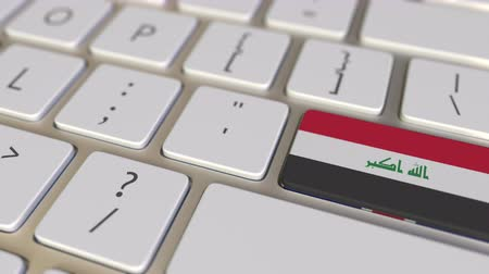 relocate : Key with flag of Iraq on the computer keyboard switches to key with flag of Great Britain, translation or relocation related animation