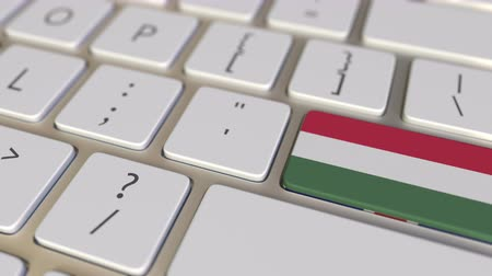 immigratie : Key with flag of Hungary on the computer keyboard switches to key with flag of Great Britain, translation or relocation related animation Stockvideo